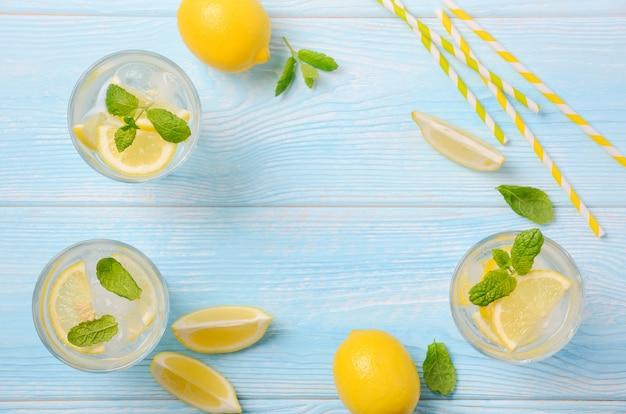 Bevanda rinfrescante fredda di estate con il limone e la menta sulla vista di legno e superiore blu-chiaro, disposizione piana, spazio della copia.