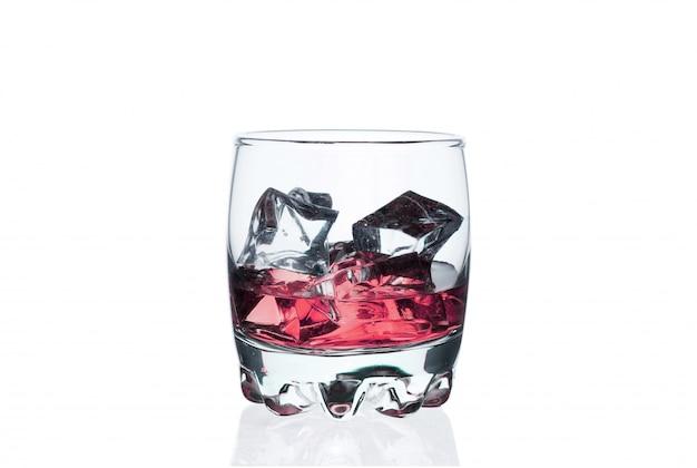 Bevanda rosa con i cubetti di ghiaccio in un vetro su bianco. cocktail freddo esotico.