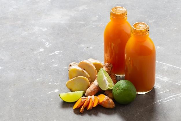 Bevanda sana dalle radici e dalla calce della curcuma e dello zenzero in piccole bottiglie sul muro di cemento grigio con copyspace.