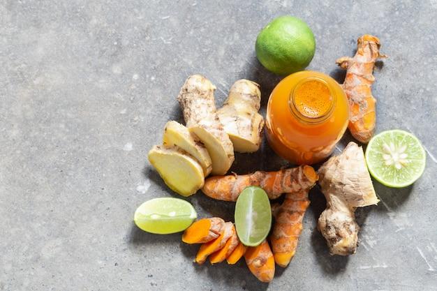 Bevanda sana dalle radici e dalla calce della curcuma e dello zenzero in piccole bottiglie sul muro di cemento grigio.