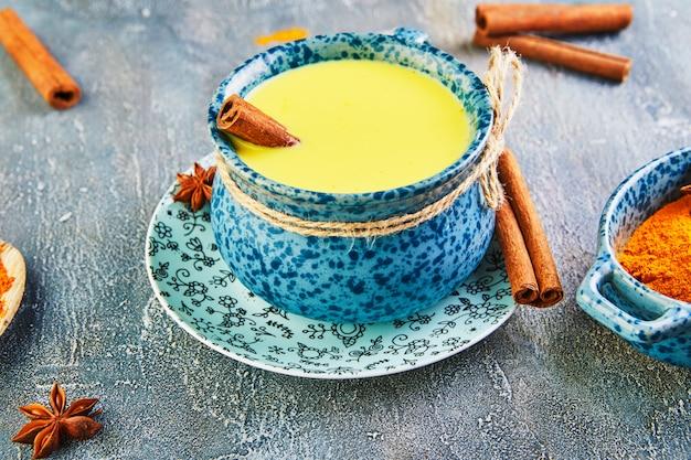 Bevanda sana della curcuma dorata del latte in una tazza blu.