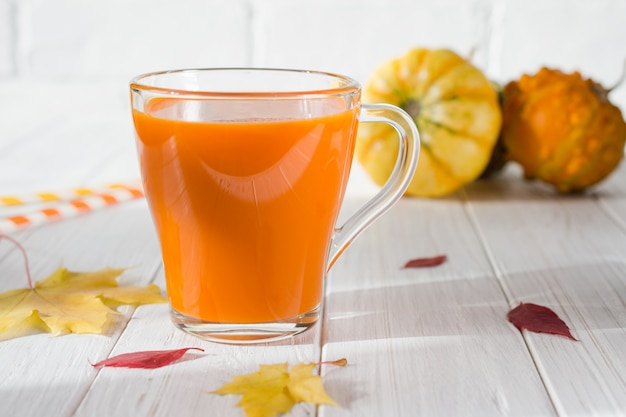 Bevanda tradizionale autunnale. tazze di vetro di succo di zucca, zucche e foglie di acero cadute
