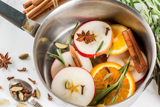 Bevanda tradizionale di natale e inverno, ingredienti per vin brulè bevanda calda con agrumi, mela e spezie in casseruola di alluminio sul tavolo di marmo bianco. copia spazio vista dall'alto