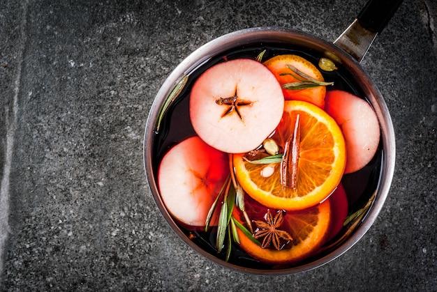 Bevanda tradizionale di natale e inverno, vin brulè bevanda calda con agrumi, mela e spezie in casseruola di alluminio sul tavolo di pietra nera. copia spazio vista dall'alto