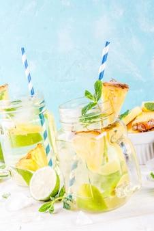 Bevanda tropicale ananas mojito o limonata con calce fresca e menta sfondo blu chiaro