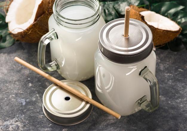 Bevanda tropicale estiva sana succo di cocco o acqua o latte in barattoli di vetro