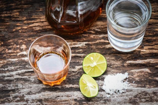 Bevande alcoliche e sale al limone su fondo di legno rustico brandy in un bicchiere con bottiglie di alcolici e acqua, vodka rum cognac tequila e whisky