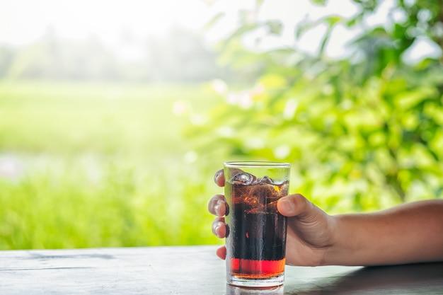 Bevande analcoliche con ghiaccio. closeup donna mano che regge un bicchiere di bevanda di cola