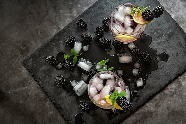 Bevande analcoliche stagionali. sete nella calda estate. due bicchieri di ghiaccio, acqua, lime e bacche di gelso alla menta. dieta chetonica, bibite e bevande alcoliche. cocktail di frutta