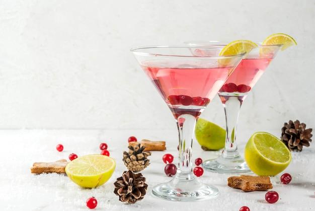 Bevande autunnali e invernali. bevanda per le vacanze di natale. mirtillo rosso festivo martini con lime. sulla tavola bianca con la decorazione di natale, copyspace
