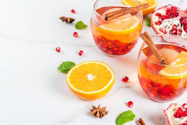 Bevande autunnali e invernali. caldo cocktail rinfrescante con melograno, arance, cannella, spezie e menta. su un tavolo di marmo bianco.