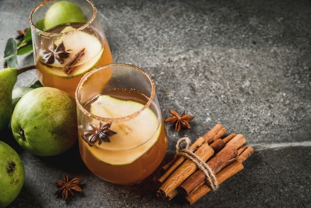 Bevande autunnali vin brulè. tradizionale cocktail autunnale speziato con sciroppo di pera, sidro e cioccolato, con cannella, anice, zucchero di canna. sul tavolo di pietra nera. copyspace