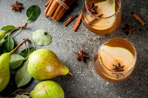 Bevande autunnali vin brulè. tradizionale cocktail autunnale speziato con sciroppo di pera, sidro e cioccolato, con cannella, anice, zucchero di canna. sul tavolo di pietra nera. vista dall'alto di copyspace