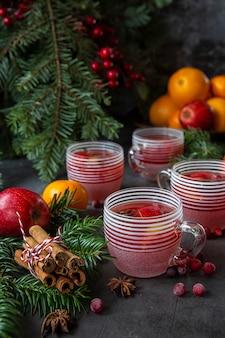 Bevande calde invernali tavolo di natale con bicchieri di vin brulè, arance, mandarini, mele, albero di natale e mirtilli rossi.