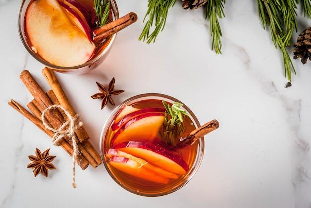 Bevande del ringraziamento di natale autunno inverno cocktail grog sangria calda vin brulè - mela rosmarino anice cannella sul tavolo di marmo bianco con coni rosmarino
