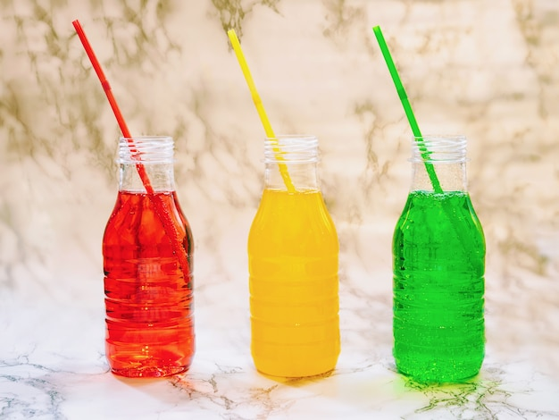 Bevande di limonata colorata naturale in bottiglie di plastica con tubi, bevande isotoniche naturali per il fitness, bevande ambientali organiche