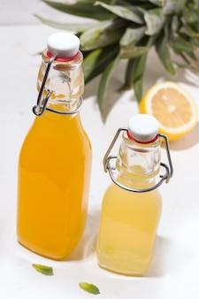 Bevande estive di ananas e limone in bottiglie di vetro