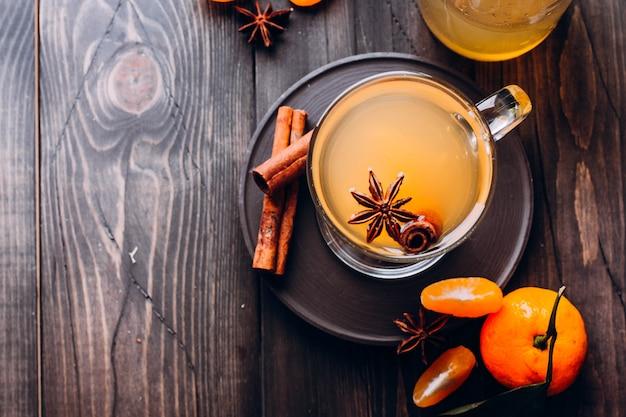 Bevande fresche con spezie, agrumi e cannella in vetro su legno