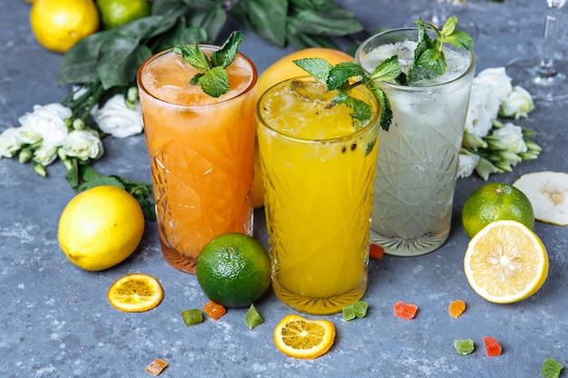 Bevande fresche fresche di bevande estive. ghiacci la limonata nella brocca e nei limoni e nell'arancia con la menta sulla tavola all'aperto.