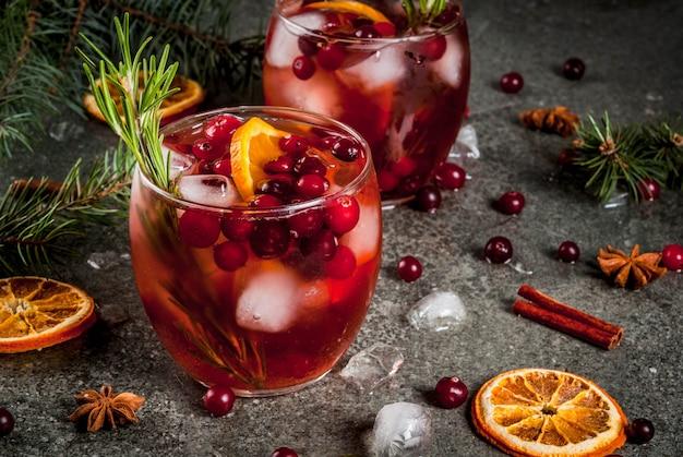 Bevande invernali di natale cocktail freddo con mirtilli rossi arancia rosmarino con spezie (anice cannella) e ghiaccio su un tavolo di pietra scura