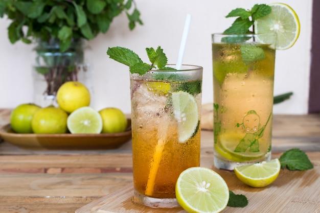 Bevande salutistiche a base di erbe succo di tè freddo al limone e succo di limone per l'assistenza sanitaria con foglia di menta piperita e fetta di limone