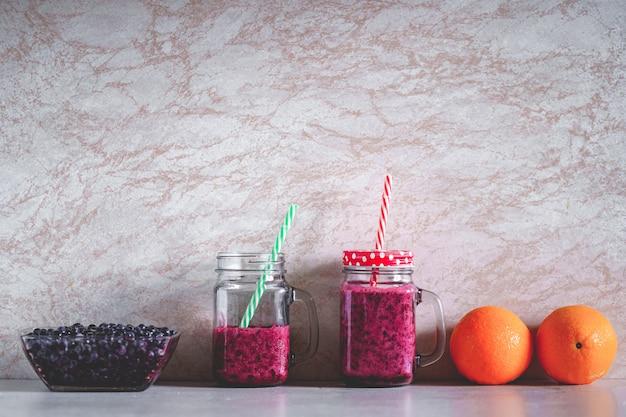 Bevande sane organiche vegetariane della bacca su fondo. pulisci il cibo vegano, mangia bene e bevi il frullato di mirtilli per la dieta