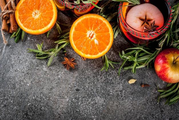 Bevande tradizionali invernali e autunnali. cocktail di natale e del ringraziamento. vin brulè con arancia, mela, rosmarino, cannella e spezie su una pietra scura, vista dall'alto