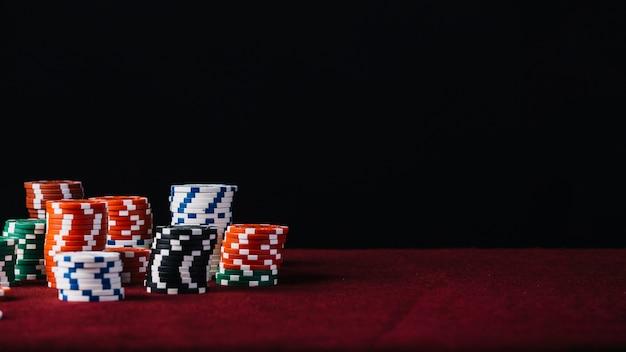 Bianca; rosso; stack di chip di casinò nero e verde sul tavolo da poker rosso