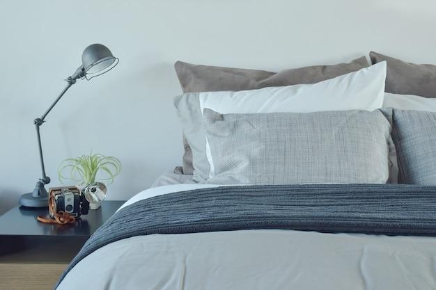 Biancheria da letto blu e grigia con lampada da tavolo in stile industriale
