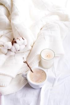 Biancheria da letto con un soffice plaid in maglia e tazza di caffè, fiori di cotone e candela.