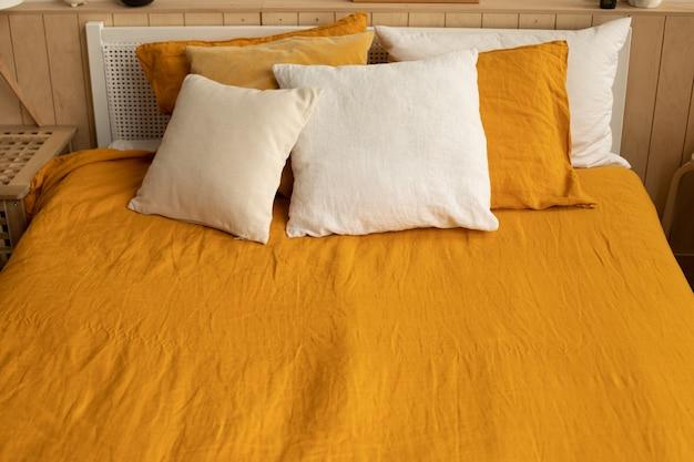 Biancheria da letto di lino arancione con cuscini bianchi e arancioni. casa accogliente