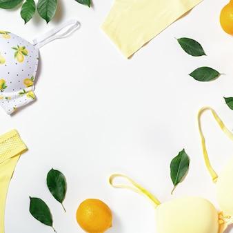 Biancheria del cotone della ragazza di estate con i limoni su fondo bianco, spazio della copia. vista piana, vista dall'alto. concetto di moda estiva