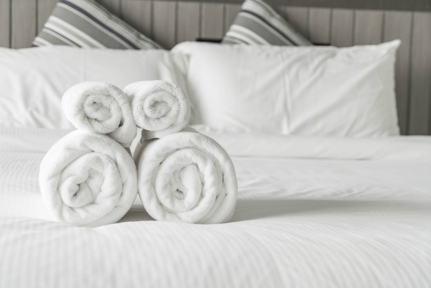 Bianco asciugamano sulla decorazione letto in camera da letto interni