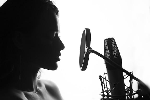 Bianco e nero. donna che canta in studio di registrazione.