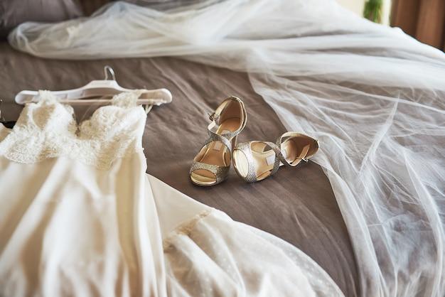 Bianco elegante abito da sposa, velo e scarpe sdraiato sul letto.