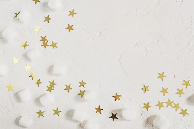 Bianco festivo con mini marshmallow e stelle dorate di coriandoli.