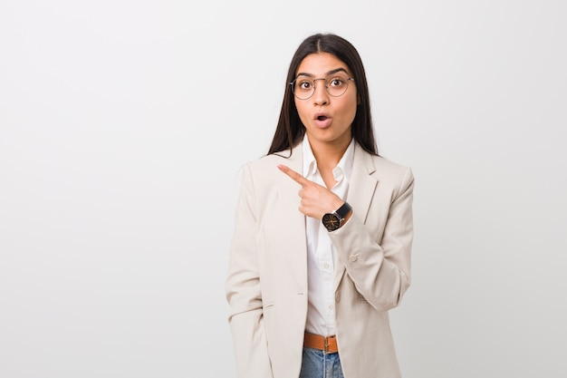 Bianco isolato giovane donna araba di affari che indica il lato