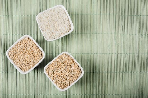 Bianco naturale; ciotole di riso crude lunghe e piatte su placemat