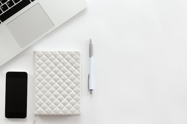 Bianco scrivania con una parte di laptop, telefono cellulare, penna