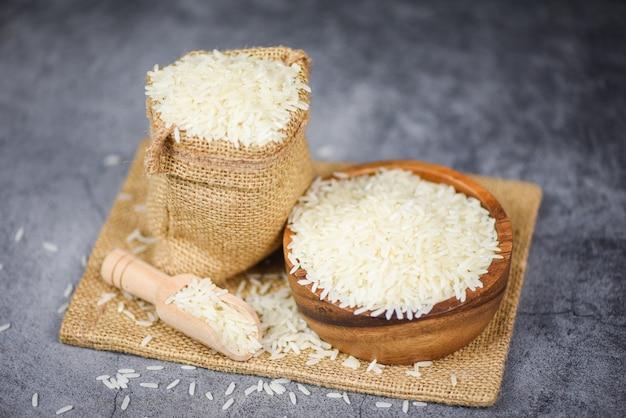 Bianco tailandese del riso sulla ciotola e sul sacco / prodotti agricoli crudi del grano del riso del gelsomino per alimento in asiatico