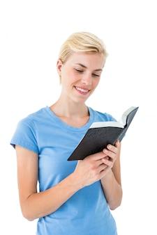 Bibbia bionda graziosa della lettura della donna