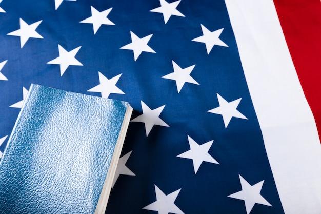 Bibbia che pone sopra una bandiera americana