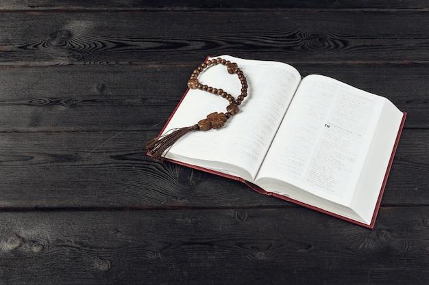 Bibbia e un crocifisso su un vecchio tavolo di legno