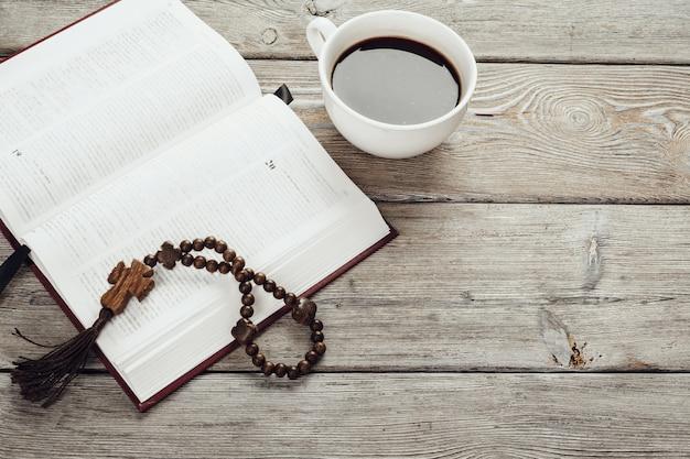 Bibbia e un crocifisso su un vecchio tavolo di superficie in legno.