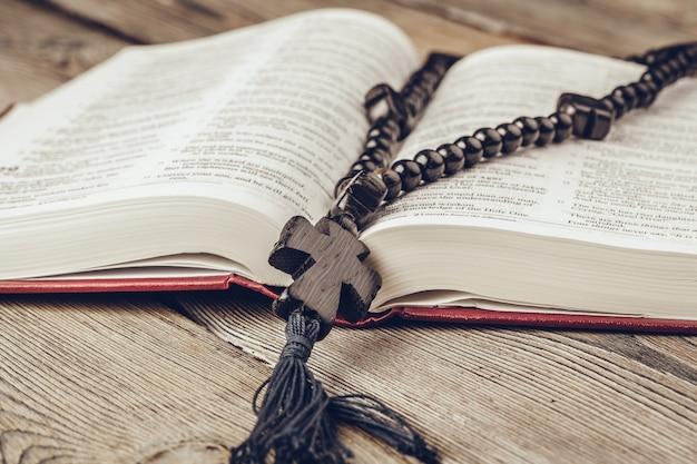 Bibbia e un crocifisso su una vecchia tavoletta di legno.