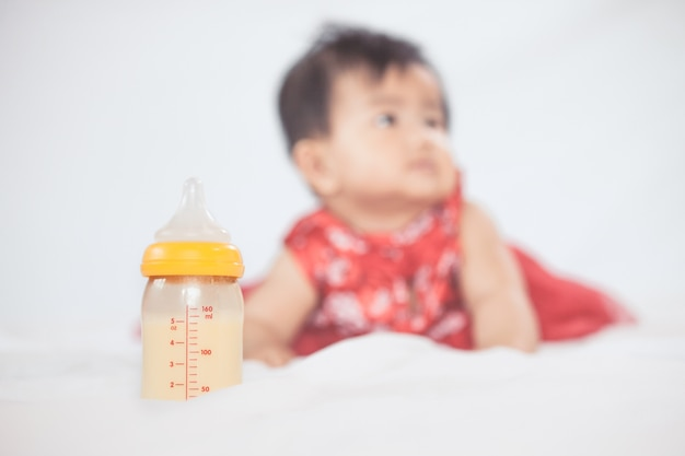 Biberon con latte materno per l'allattamento al seno sul piccolo fondo della neonata.