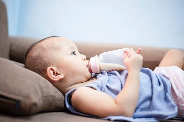 Biberon del bambino - ritratto del primo piano della bottiglia per il latte della tenuta del bambino dell'asia e di alimentazione sul sofà
