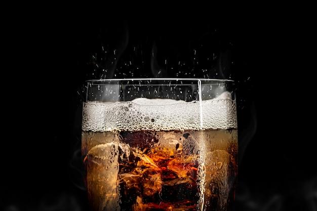 Bibita analcolica con spruzzi di ghiaccio. bicchiere di coca con rinfresco estivo.