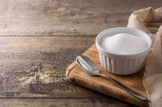 Bicarbonato di sodio in ciotola bianca sulla tavola di legno, spazio della copia