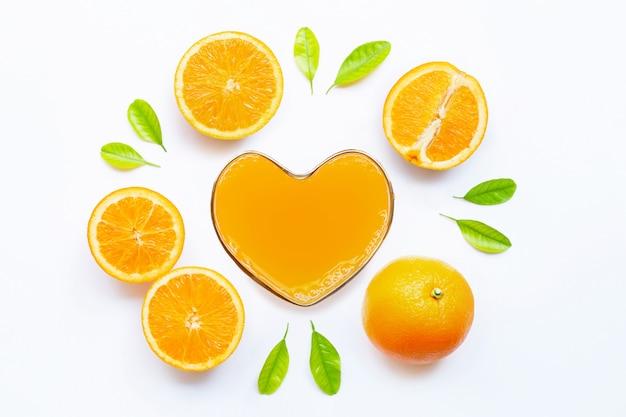 Bicchiere a forma di cuore di succo d'arancia fresco con frutta all'arancia. vista dall'alto